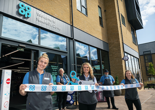 Amy and team cut the ribbon to declare Newhall Co-op open to serve community